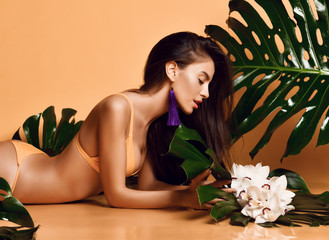 Young beautiful sexy woman with perfect smooth skin hold tropical leaves and orchid flowers on yellow background