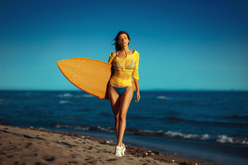 Young woman with a surf board on the beach by the sea