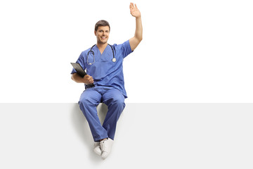 Young male doctor in a blue uniform sitting on a white panel and greeting with hand
