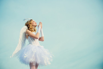 A beautiful teen with blonde curly hair as cupid - Valentines Day. Valentines day. Little angel in love. Girl angel with halo in white angel dress.