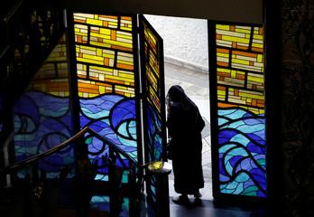 A devotee leaves a La Luz del Mundo (The Light of the World) church after its leader Naason Joaquin Garcia was arrested in California, in Mexico City