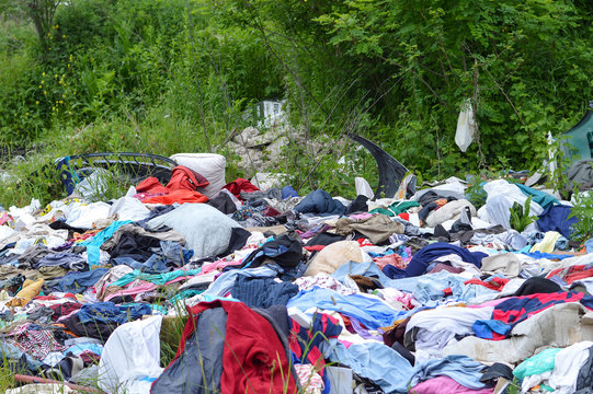 Garbage dump in nature. Environmental pollution. Abandoned clothes in nature