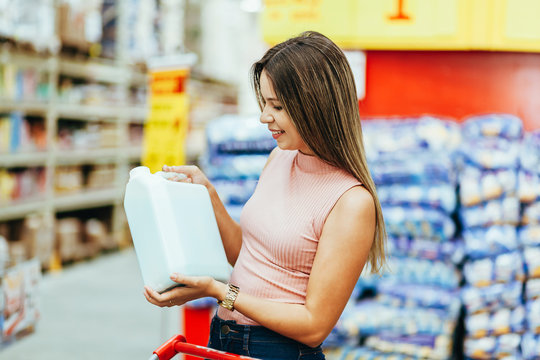 Woman choosing household products in grocery store