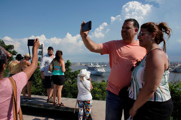 People take pictures as the cruise ship MS Empress of the Seas, operated by Royal Caribbean International, leaves the bay of Havana