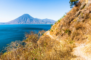 Winding dirt clifftop footpath with arid vegetation & view across Lake Atitlan to San Pedro volcano in Guatemalan highlands, Central America
