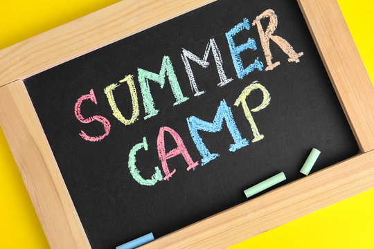 Blackboard with words SUMMER CAMP and colorful chalk on yellow background, closeup