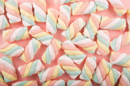 Top view on background texture of colorful twisted marshmallow candies. Copy space for your text.