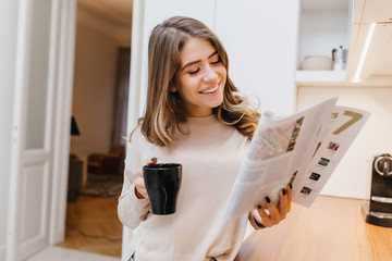 Magnificent girl reading magazine with smile in her room. Portrait of curious brunette lady with black cup enjoying good morning.