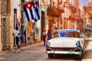Cuban flags,old car and  decaying buildings in Havana