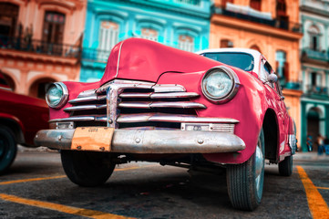 Old car painted hot pink and colorful buildings in Havana