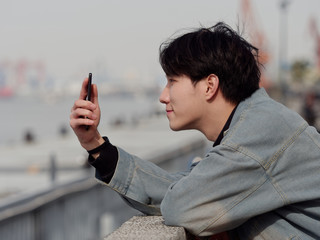 Portrait of a handsome Chinese young man holding his mobile phone, looking for something interesting in internet, mobile phone and the internet take up a lot of teenager's time.