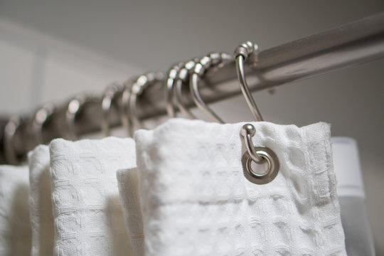 Decorative luxurious shower curtain on hooks.