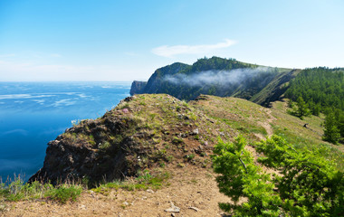 Baikal Lake in summer day. The path along the rocky shore off Olkhon Island. Tourist routes around the island. Beautiful landscape with mist on mountain
