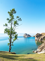 Baikal Lake summer afternoon. View of the natural attraction of Olkhon Island - Shamanka Rock and Burhan Cape. Lake natural background. Beautiful landscape