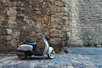 Silver scooter at street of European old city