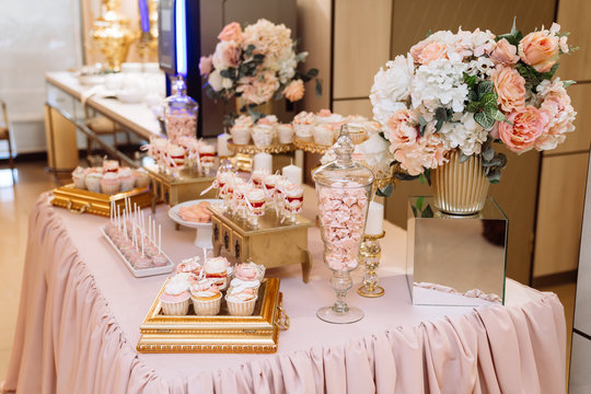 Candy bar on table in vase and plate, macaroon, marshmallow, cake and cupcake