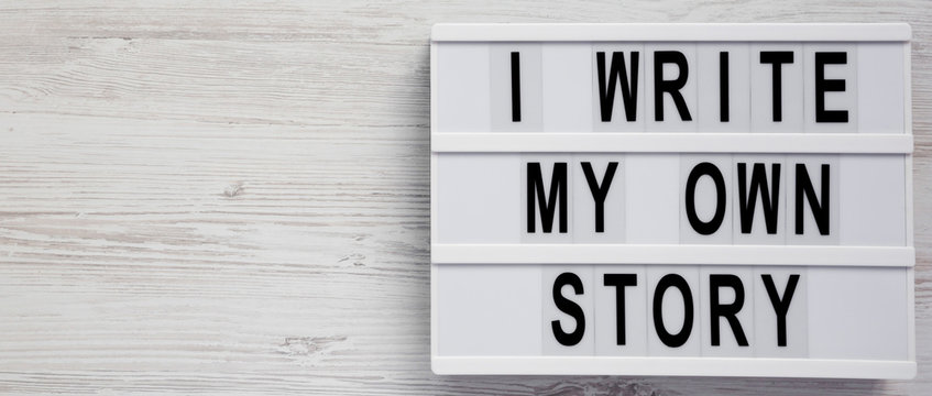 'I write my own story' words on a modern board on a white wooden background, top view. From above, overhead, flat lay. Copy space.