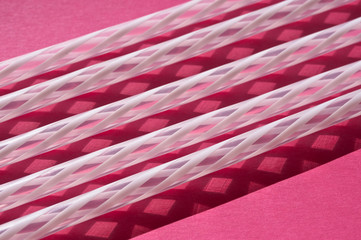White straws on pink background strong shadow