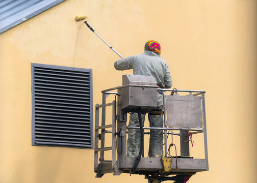 Man on a lifting platform painting the building wall with a roller exterior outdoors. Worker on a ladder manually painting yellow wall on construction site