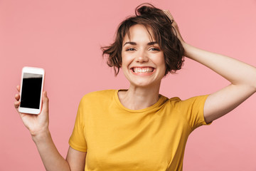 Wall Mural - Happy young beautiful woman posing isolated over pink wall background using mobile phone.