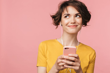Wall Mural - Happy young beautiful woman posing isolated over pink wall background listening music with earphones using mobile phone.