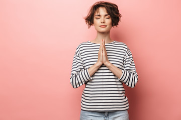 Pleased beautiful woman posing isolated over pink wall background meditate.
