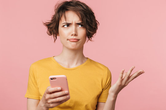 Confused young beautiful woman posing isolated over pink wall background using mobile phone.