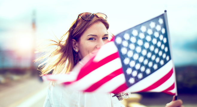 Young patriot modern woman holding USA flag depth of field