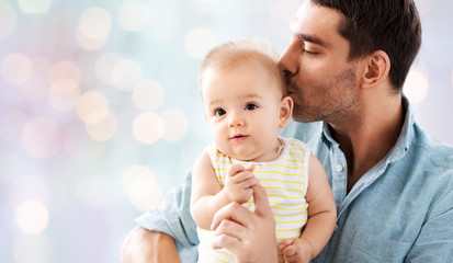 family, parenthood and people concept - happy father kissing little baby daughter over lights background Wall mural