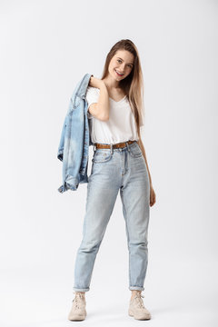 Stylish young woman in jeans on white background