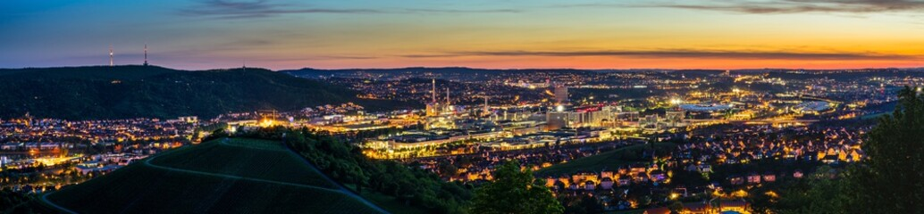 Germany, XXL panorama of magic illuminated skyline of downtown stuttgart city houses and arena after sunset from above