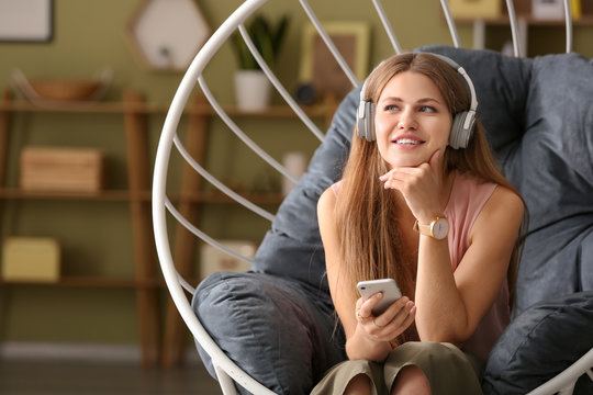 Young woman listening to audiobook at home