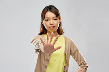 people, prohibition and rejection concept - young asian woman showing stop gesture over grey background