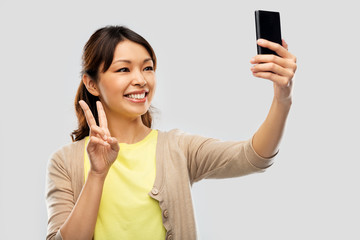 bf7d866654 technology and people concept - happy asian woman taking selfie by  smartphone and showing peace over