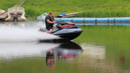 A man on a jet ski quickly rides on the river against the background of fishing boats near the shore on a summer day