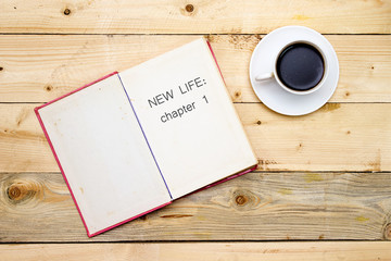 New life: chapter 1 on open book on woodne table