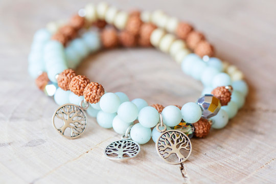 Mineral stone amazonite and tree pendant bead bracelet on natural wooden background
