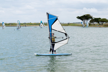 young teenager woman windsurfing on the lake of the island of re windsurf board