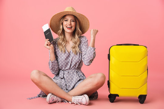 Excited young pretty woman tourist posing isolated over pink wall background with suitcase holding passport with tickets.
