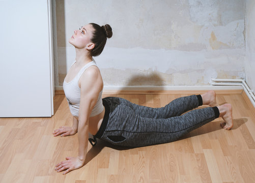 sporty young woman performing yoga stretching exercise on the floor at home - Bhujangasana or cobra pose