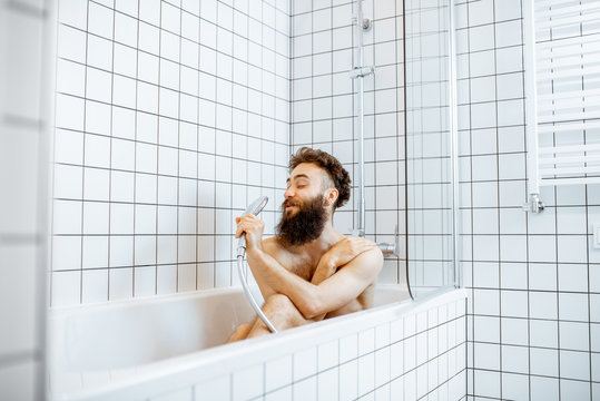 Joyful bearded man washing in the bathtub, having fun singing into the shower in the bathroom