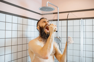 Joyful bearded man singing into the micrphone while taking a shower in the bathroom Fotobehang