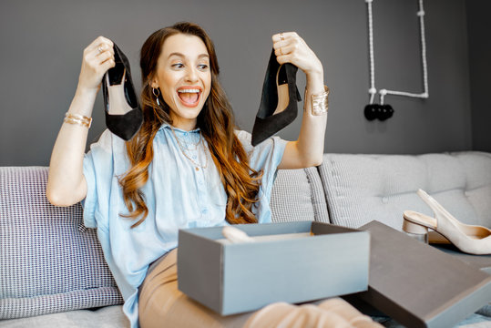 Portrait of a young woman excited with a new purchases, holding beautiful shoes while sitting on the couch at home
