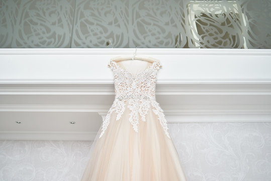 Beautiful beige embroidered wedding dress hanging on hanger against wall in luxury hotel room, copy space, close up. Bridal morning preparations. Wedding concept
