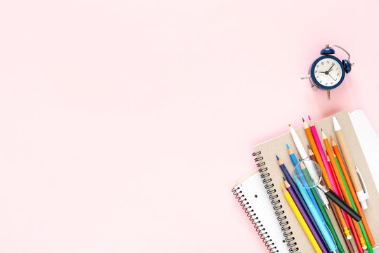 School stationary on pink background. Notebooks, pens, color pencils and alarm clock. Back to School concept.