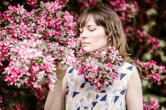Woman smelling pink flowers outdoor