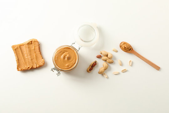 Flat lay composition with peanut butter sandwich, glass jar, peanut and spoon on white background, space for text