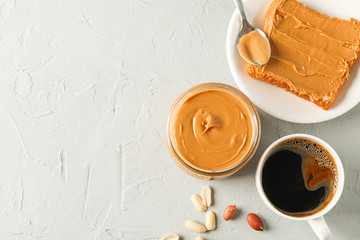 Glass jar with peanut butter, peanut, cup of coffee, spoon and peanut butter sandwich on grey background, top view and space for text