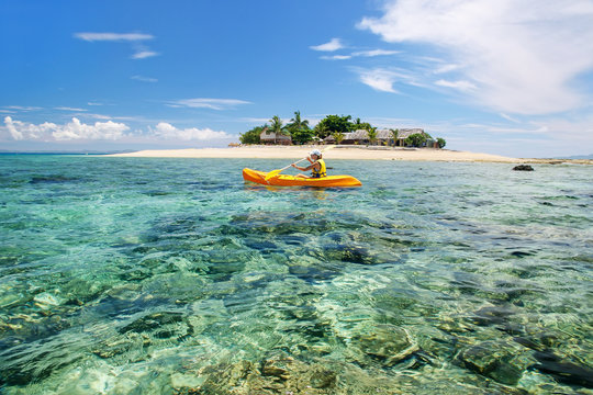 Young woman kayaking near South Sea Island, Mamanuca islands group, Fiji