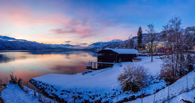 Beautiful view on Millstätter lake in Austria. The lake is surrounded by Alps. Mountains are covered with snow. The sky is exploding with pink and orange. Stunning sunset. Little cottage on the side.
